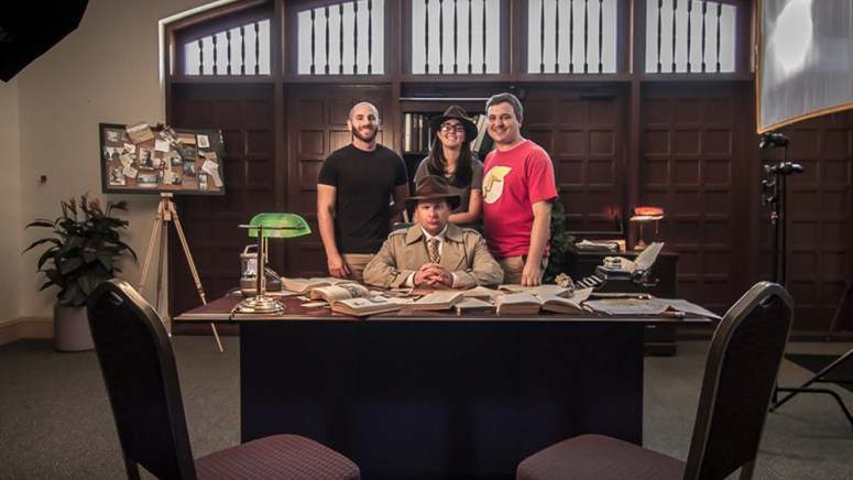 Left to Right: Shelby Halberg, the director of photography, Kat Brady, the director, Josh Brady, the producer, and Gregg Goldsbury, the lead actor, all stand together on the set of detective dick's office.